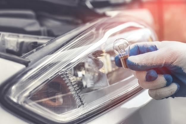 Reparador en autoshop muestra la bombilla de luz de un coche nuevo para su reemplazo, faro en el fondo. luz de la lámpara
