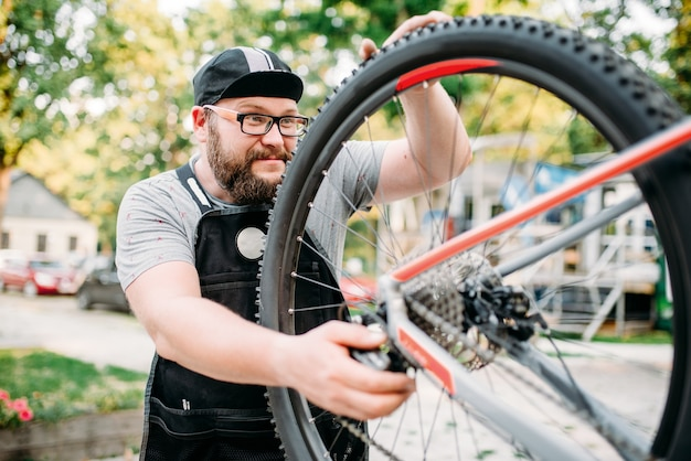 El reparador de bicicletas trabaja con rueda de bicicleta, taller de ciclo al aire libre. mecánico barbudo en delantal