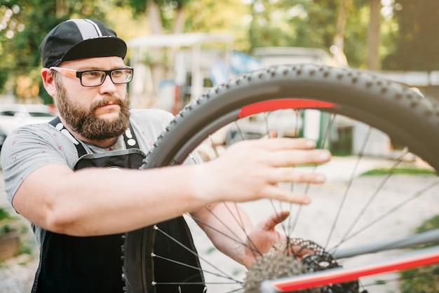 Reparador de bicicletas trabaja con rueda de bicicleta