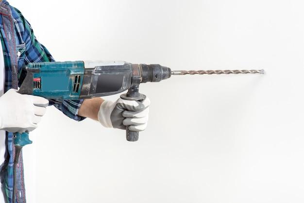 Reparador en un casco protector y gafas perfora una pared blanca con una perforadora, durante la construcción