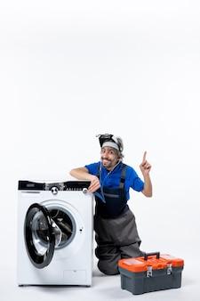 Reparador eufórico de vista frontal sentado cerca de la lavadora levantando la mano en el espacio en blanco