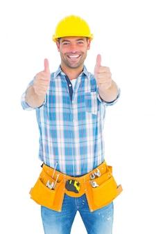 Reparador feliz que gesticula los pulgares en el fondo blanco