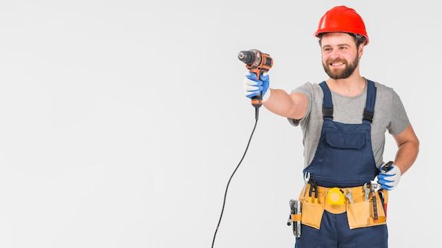 Reparador feliz en taladro de explotación general en la mano