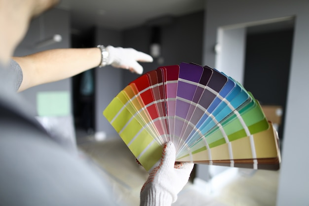 Reparador en guantes de pie en plano, mirando las paredes y la paleta e intentando elegir el color para los detalles interiores. reparador profesional durante el concepto de trabajo.