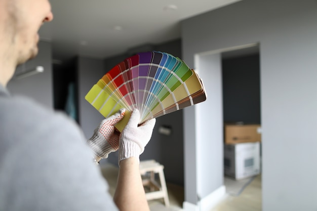 Reparador en guantes de pie en plano, mirando a las paredes y tratando de elegir el color para los detalles interiores. reparador profesional durante el concepto de trabajo.