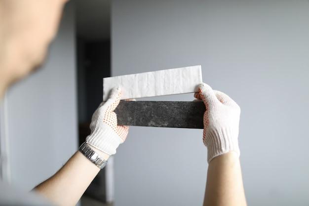 Reparador en guantes que elige el color correcto de los materiales para los detalles interiores sobre paredes grises de fondo. reparador profesional durante el concepto de trabajo.