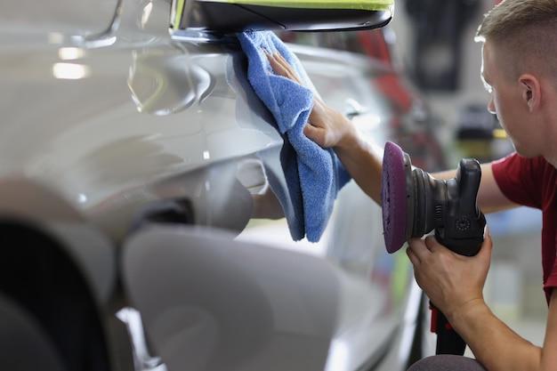 Reparador de hombre limpiando el coche con un paño de microfibra y sosteniendo la máquina pulidora en su mano