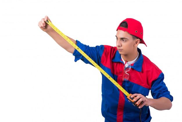 Reparador joven con cinta métrica aislado en blanco