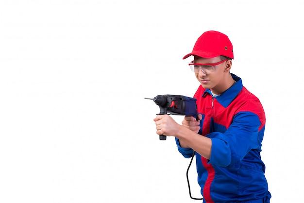 Reparador joven con el perforador del taladro aislado en blanco