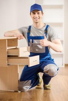 Reparador joven que ensambla la nueva tabla en el interior casero.