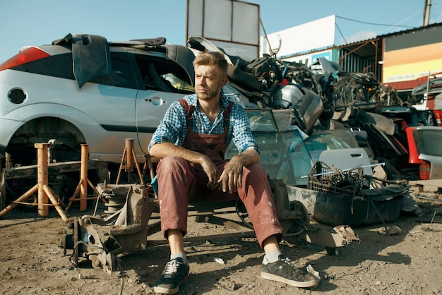 Reparador masculino sentado en el suelo, depósito de chatarra de coches