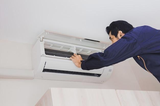 Reparador mecánico de aire en uniforme azul está comprobando el aire acondicionado