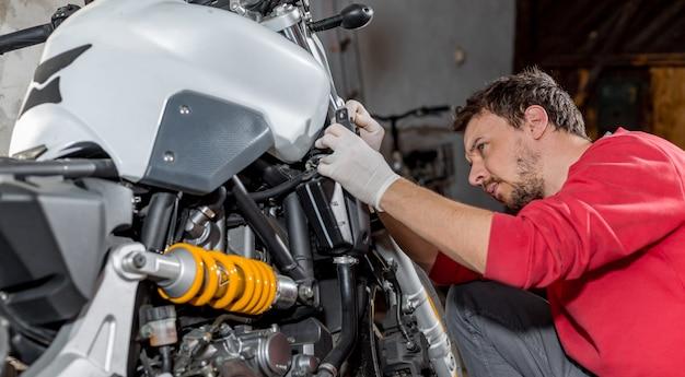 Reparador mecánico haciendo mantenimiento o reparación, fijación en la motocicleta, moto, centro de servicio