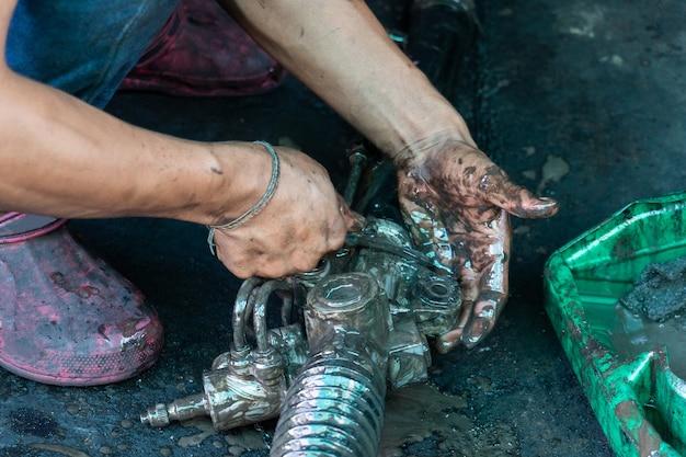 Reparador del motor está utilizando aceite de motor para lavar partes del motor.