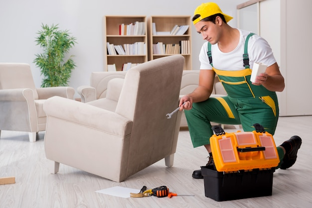 Reparador de muebles reparando sillón en casa.