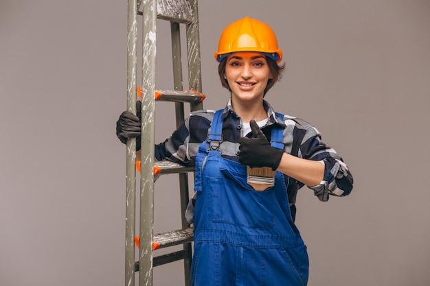 Reparador de mujer con escalera en un uniforme aislado