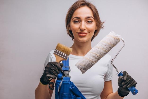 Reparador de mujer con rodillo de pintura aislado