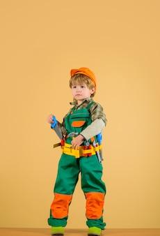 El reparador del niño pequeño sostiene la sierra en la mano el trabajo con las herramientas la reparación del niño pequeño en el uniforme del constructor con