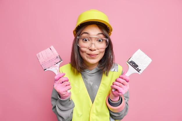 Reparador profesional sostiene pinceles vestidos de uniforme y casco