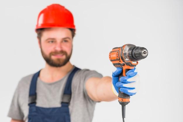Reparador que sostiene el taladro en la mano
