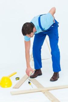 Reparador recogiendo destornillador mientras sufre de dolor de espalda