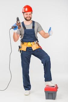 Reparador con taladro mostrando pulgar arriba