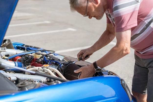 El reparador trabaja con el automóvil, reemplazando el filtro de aire de admisión del cilindro.