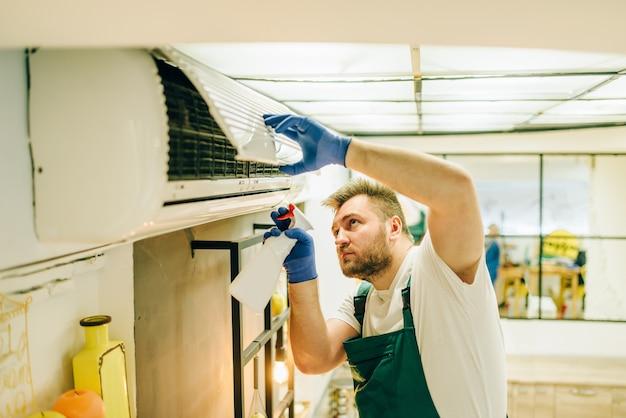 Reparador en uniforme limpia el aire acondicionado