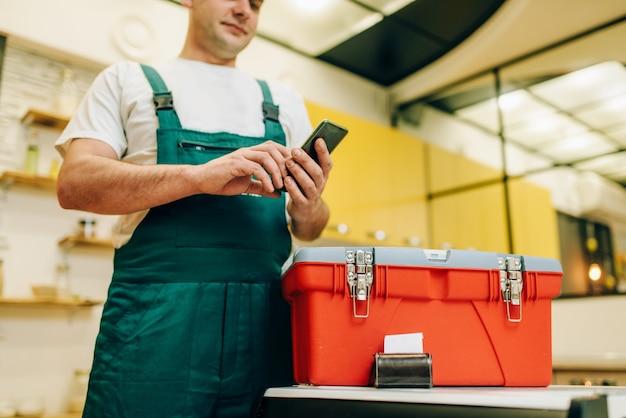 Reparador en uniforme sostiene el teléfono contra la caja de herramientas, manitas.