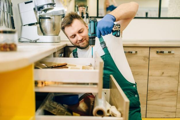 Reparador en uniforme tiene destornillador, técnico. trabajador profesional hace reparaciones en la casa, servicio de reparación del hogar