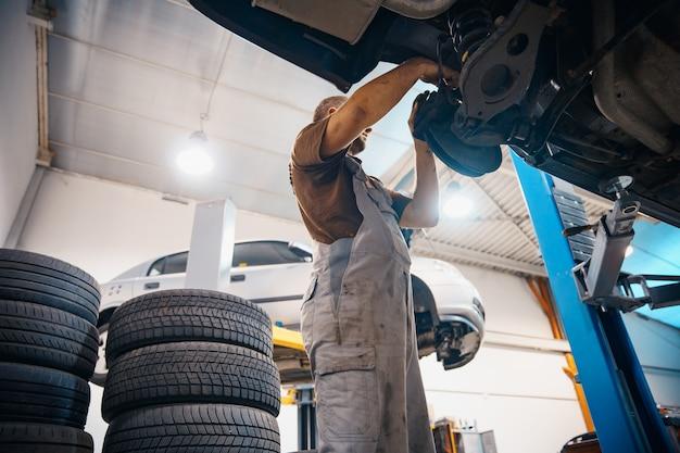 Repare y revise el automóvil en el taller de reparaciones. un técnico experimentado repara la parte defectuosa del automóvil. cambio neumáticos