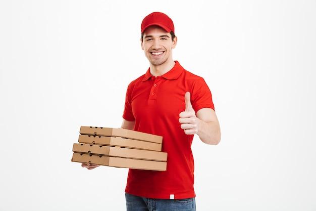 Repartidor 25 años en camiseta roja y gorra con pila de cajas de pizza y gesticulando pulgar hacia arriba, aislado sobre espacio en blanco