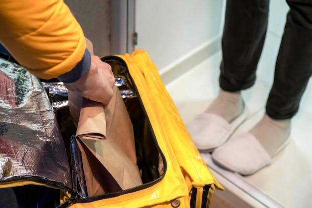 Repartidor abriendo mochila amarilla y tomando una bolsa con orden, piernas de otro hombre