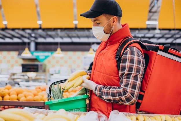 Repartidor de alimentos comprando productos en la tienda de comestibles