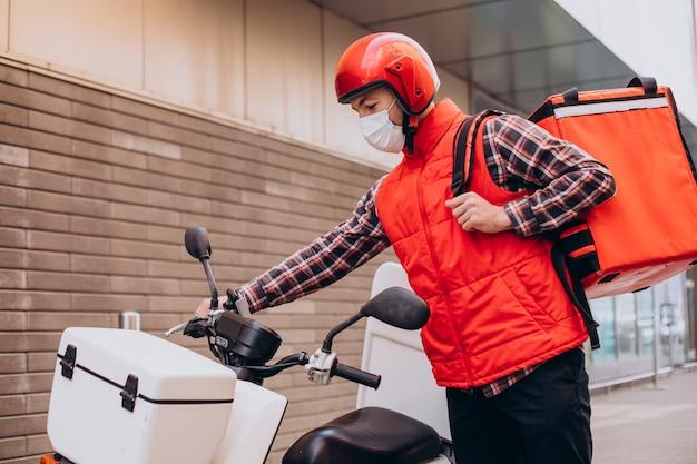 Repartidor de alimentos conduciendo scooter con caja con comida y máscara con máscara