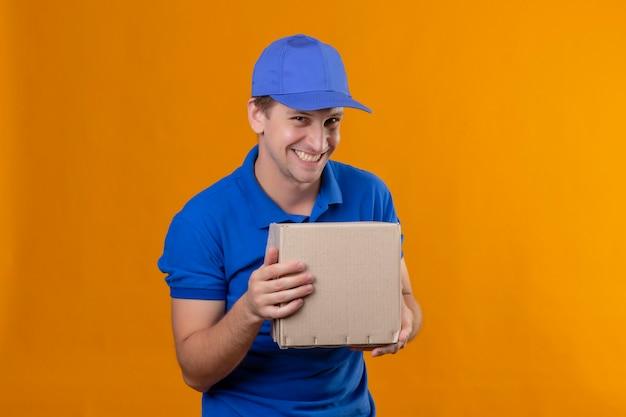 Repartidor apuesto joven en uniforme azul y gorra con paquete de caja sonriendo astutamente feliz y positivo de pie sobre la pared azul