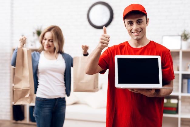 Repartidor árabe con laptop y chica con packege