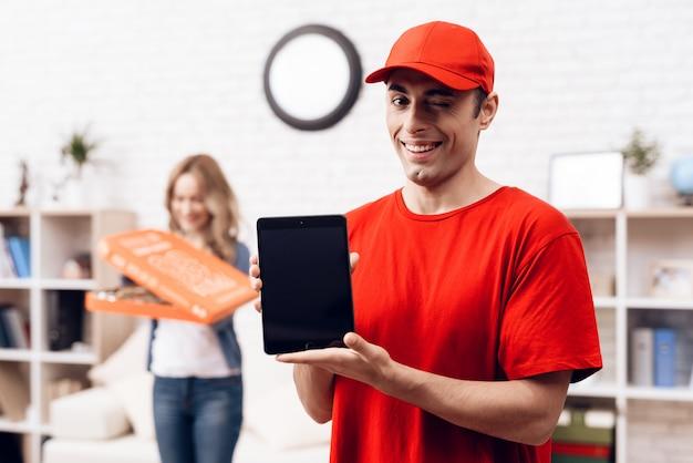 Repartidor árabe con tableta y chica con pizza.