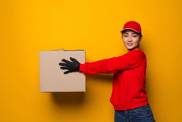 Repartidor asiático joven que sostiene la caja aislada en amarillo