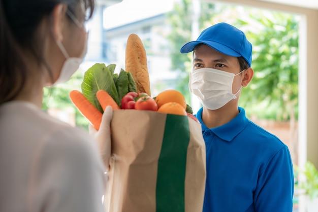 Repartidor asiático con mascarilla y guante con comestibles bolsa de comida, fruta, verdura dar a la mujer cliente frente a la casa durante el tiempo de aislamiento en el hogar.