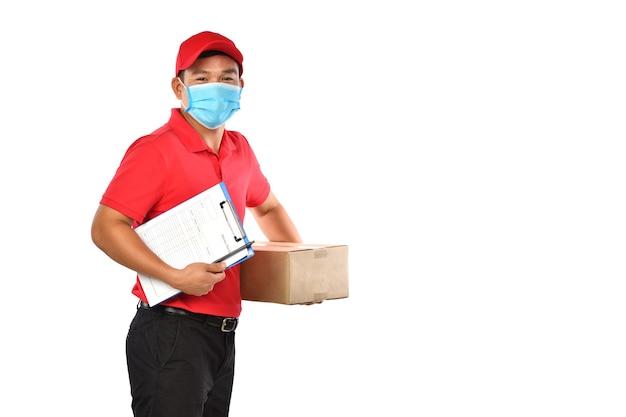 Repartidor asiático con mascarilla y guantes en uniforme rojo entregando caja de paquetería aislada sobre fondo blanco durante el brote de covid-19