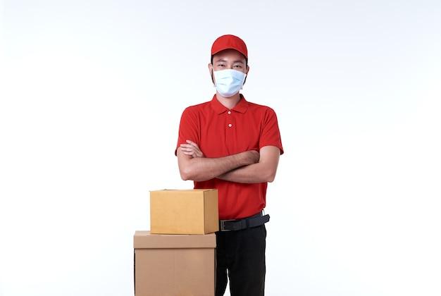 Repartidor asiático con mascarilla en uniforme rojo y caja de paquetería sobre blanco.