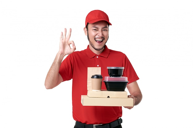 Repartidor asiático con uniforme rojo con caja de almuerzo y café para llevar aislado sobre fondo blanco. servicio de entrega urgente durante covid19.