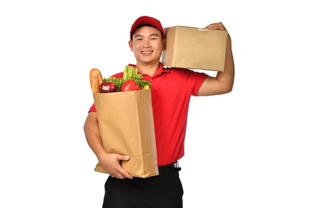Repartidor asiático en uniforme rojo lleva caja de cartón de paquete y bolsa de supermercado aislado sobre fondo blanco.