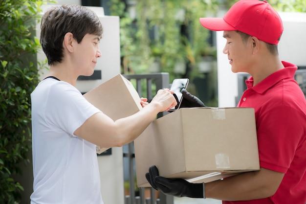 Repartidor asiático en uniforme rojo que entrega la caja del paquete al destinatario de la mujer en casa con el signo del destinatario para recibir el paquete en un dispositivo inteligente