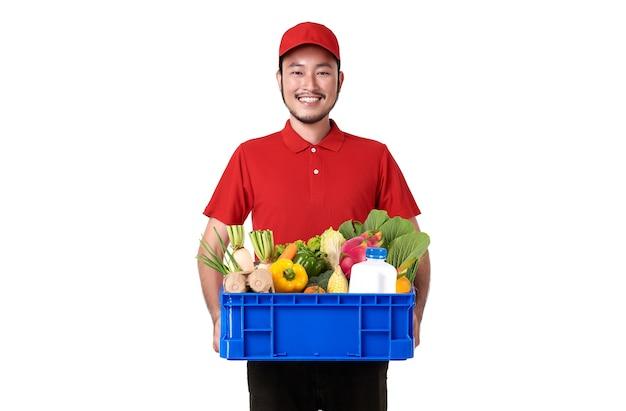 Repartidor asiático vistiendo uniforme rojo con canasta de comida fresca aislada sobre pared blanca.