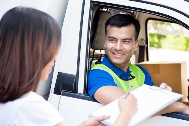 Repartidor en el auto entregando el paquete a una mujer y dando su documento para firmar