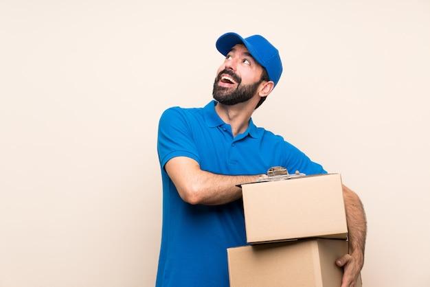 Repartidor con barba sobre aislado mirando hacia arriba mientras sonríe