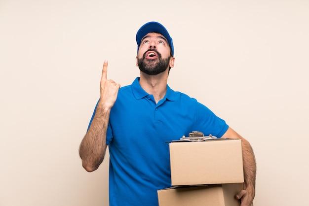 Repartidor con barba sobre pared aislada apuntando hacia arriba y sorprendido