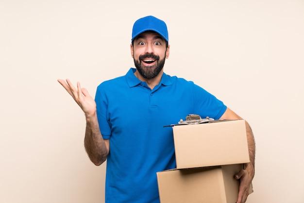 Repartidor con barba sobre pared aislada con expresión facial sorprendida